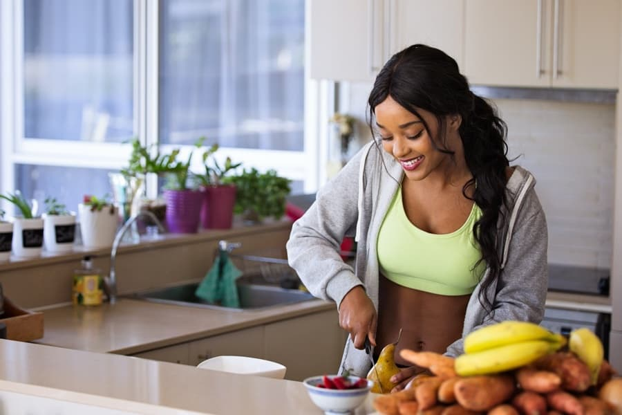 a woman cuts up healthy food in the kitchen in an effort to lose weight