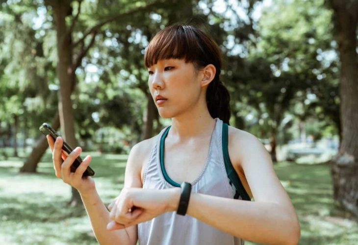 a woman checks her weight loss app on her smartphone