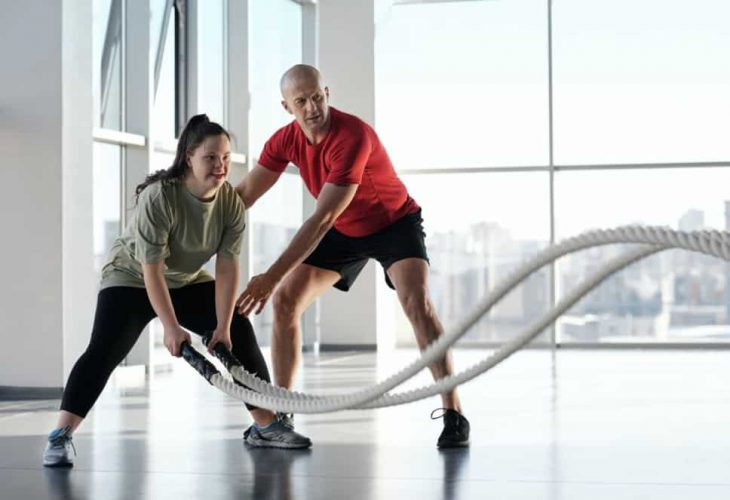 a woman and her trainer workout with battle ropes