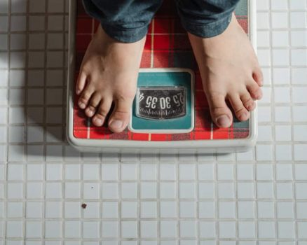 a man steps on the scale to see how much weight he has lost