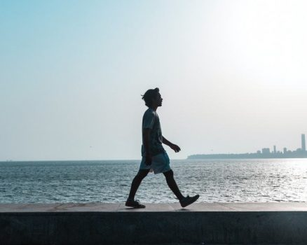 a man walks near the ocean as part of his new weight loss routine